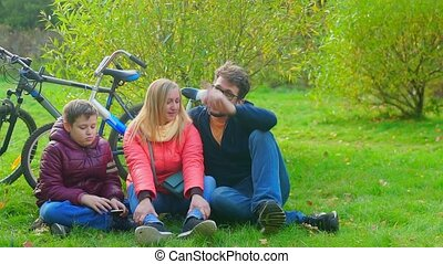 Teen boy sitting with mom and dad on the grass