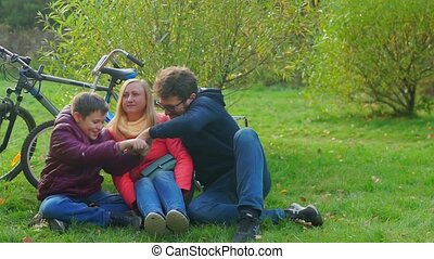 Teen boy sitting with mom and dad on the grass. Smartphone addiction.