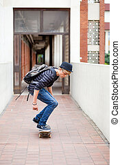teen boy skateboarding in school passage