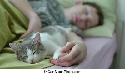 teen boy sleep with cat in bed hug close up. cat and boy...