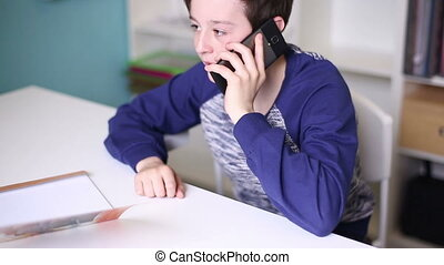 Teen Boy Talking by Smartphone - Teenager sitting at a table...