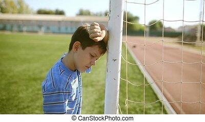 Teen boy upset defeat by knocking goal goal post net stadium...