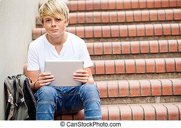 teen boy using tablet computer in school