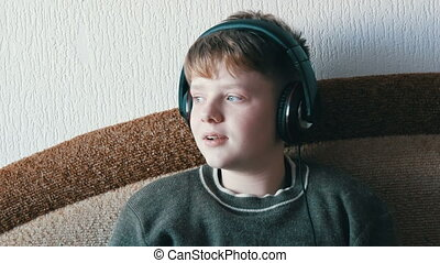 Teen boy with big headphones on his head is listening to music and sing while sitting on a brown sofa.