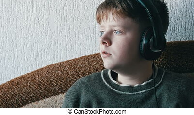Teen boy with big headphones on his head is listening to...