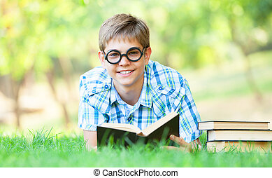 Teen boy with books in the park.