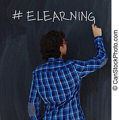 Teen Boy with chalk writing on black chalkboard hashtag elearning