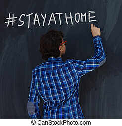 Teen Boy with chalk writing on black chalkboard hashtag stay at home