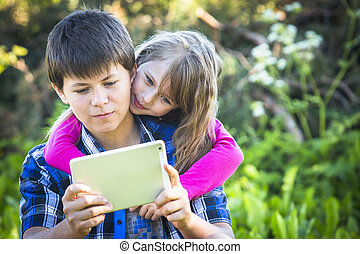 Teen boy with his younger sister sitting in a Park and using the tablet.