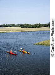 Two teenage boys kayaking through marshland on Bald Head Island, North Carolina.