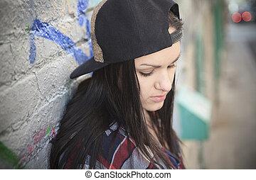 A teen wearing a cap on a beautiful street