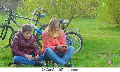 teen chłopiec, posiedzenie, następny, mamusia, trawa, interpretacja, smartphone.