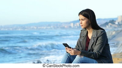 Teen checking phone and looking at horizon on the beach -...