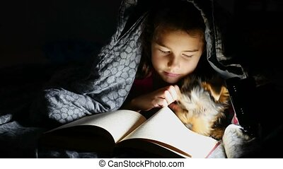 teen child reading girl reads a book at night with flashlight lying under a blanket
