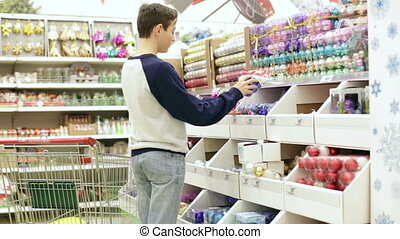 A teenager in the shop takes off the shelf Christmas ornaments. Teen in store puts a Christmas multicolored and blue balls in cart