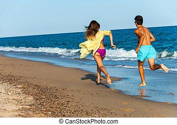 Teen couple chasing on beach.