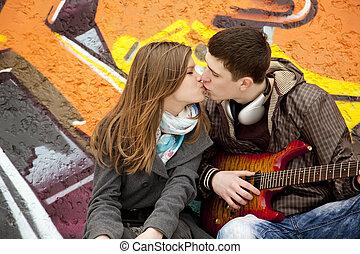 Teen couple kissing at graffiti background.