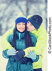 Teen couple kissing in winter park.