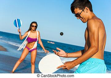 teen couple playing smash ball beach tennis. - Teen couple...