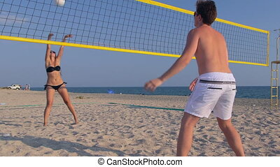 Teen couple playing volleyball on the beach