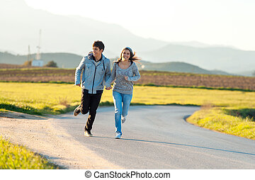 Teen couple running in countryside.