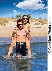 Teen couple running piggyback on summer beach
