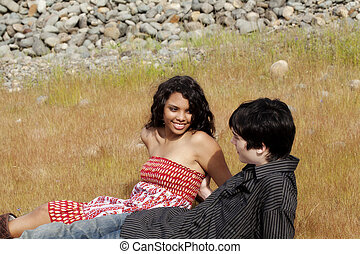 Teen Couple Sitting In Grass Outdoors Together