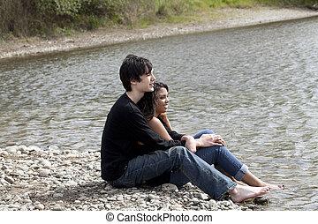 Teen couple sitting on stony river bank