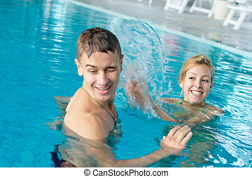 Teen couple splashing in a pool