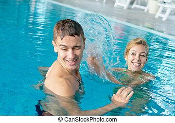Teen couple splashing in a pool