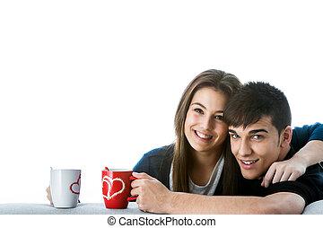 Teen couple with coffee mugs.