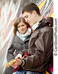 Teen couple with guitar at graffiti background.