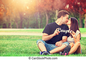 Teen couple with word Couple in the park