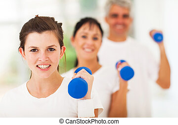 teen daugther exercising using dumbbell with parents