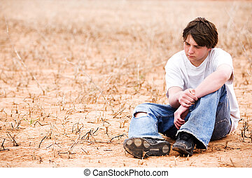 teenager sitting depressed in dry lakebed amongst the weeds, contemplating.