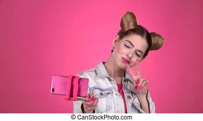 Teen doing selfie on selfie stick. Pink background. Slow motion
