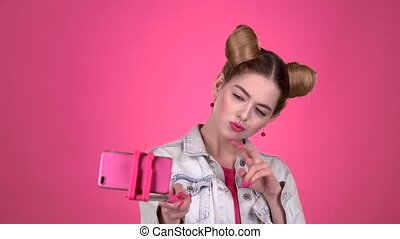 Teen doing selfie on selfie stick. Pink background