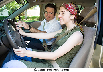 Teen girl taking driving lessons from an instructor or her father.