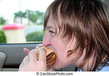 Teen Eating Cheeseburger In Car