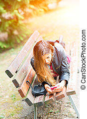 Teen face down on a bench writing sms
