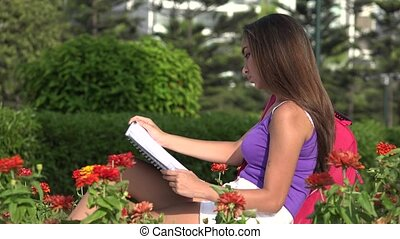 Teen Female Student Reading Notebook