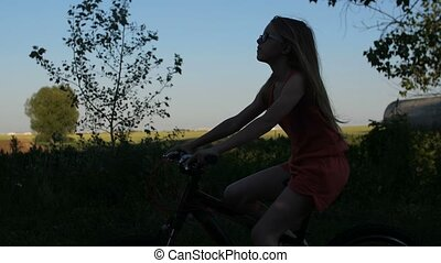 Teen female with long hair cycling in nature