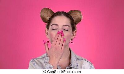 Teen flirts and sends an air kiss. Pink background -...