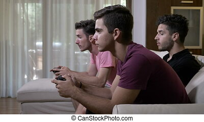 Teen friends sitting on a couch spending time playing a...