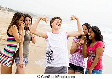 teen fun - teen girls chuckling at a teen boy showing his...