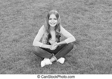 teen girl after hairdresser. relax on green grass. spring leisure time. happy childhood. kid with stylish hair. cheerful smile. happy little girl has long curly hair. kid beauty and fashion