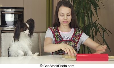 Teen girl and dog Papillon prepare cookies, rolling dough...