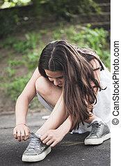 teen girl binding shoelace