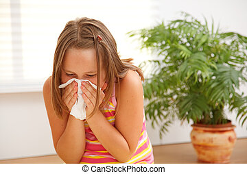 Teen girl blowing out her nose because of allergic reaction...