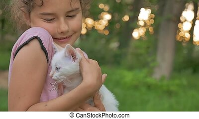 girl brunette holding kitten in her cat arms love outdoors